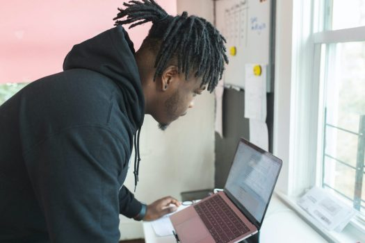 a man with dreadlocks leans over a laptop