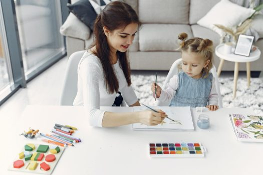 a woman and child paint together doing a spring art project