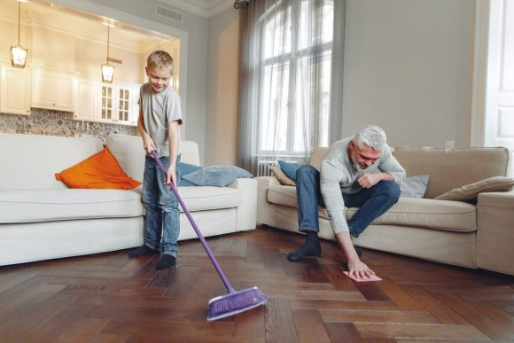 An older man and a young boy clean a floor together