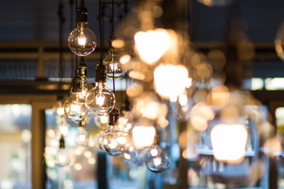 A bright bokeh effect photo of Edison light bulbs in the foreground and blurry bright lights in the background.