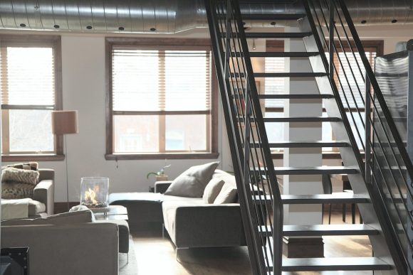 A condo living room with metal stairs and neutral colors furnishing