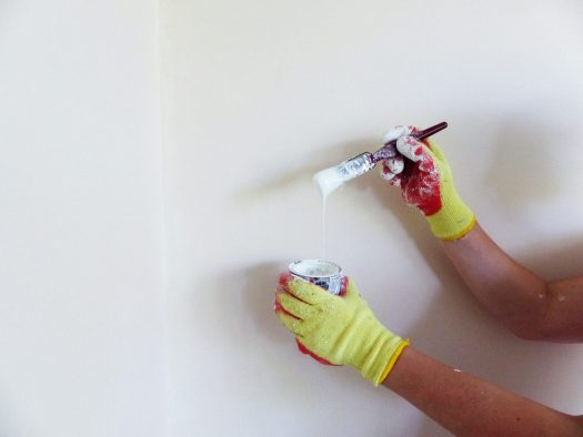 A pair of hands in yellow work gloves is holding a can of white paint and a paintbrush dripping white paint.