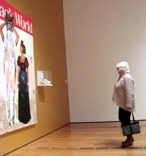 Mujer en el museo que ve la obra del artista local Fahamu Pecou.