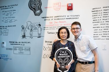 A man and a woman stand in front of a white board covered with science-related illustrations