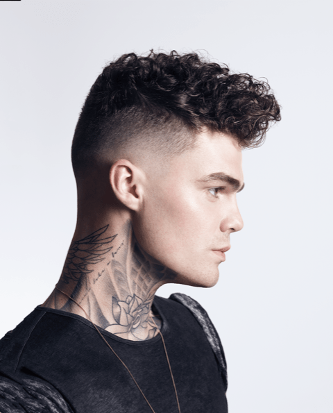 a male with neck tattoos and a fashionable haircut