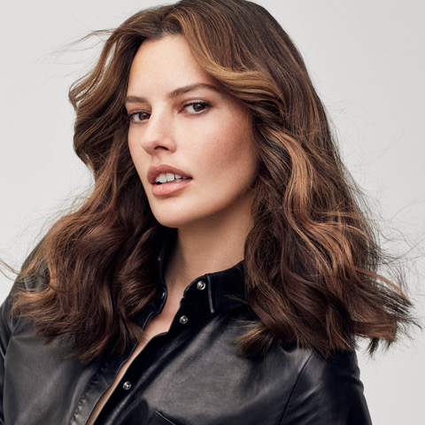 a woman in a leather jacket with brown hair gives the camera a sultry look