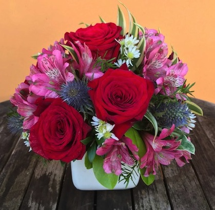 """Sometimes a little bit goes a long way.....3 premium red roses, passionate pink astromerias and assorted fresh flowers simply stand out in this small ceramic planter. Approx. size 9x9"""". Price: $48"""