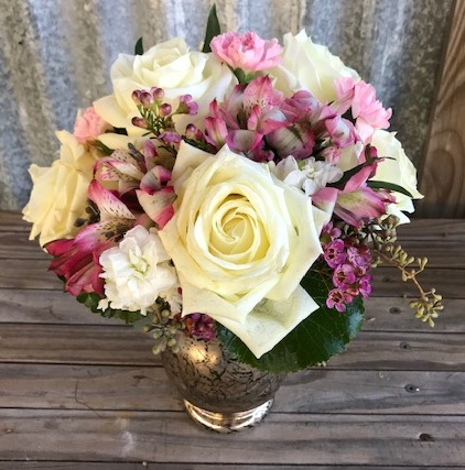 """Creamy white roses innocently blend amidst assorted blush blooms in this distressed glass vessel. Flowers include 5 white roses, astromerias, eucaliptus. Approx. 12x9"""". Price: $58"""
