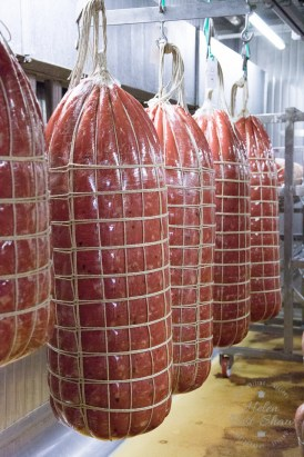 Freshly cooked Mortadella Bologna hanging in the air oven