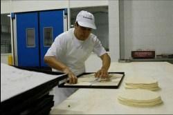 haciendo pizzas en empresa de alimentos