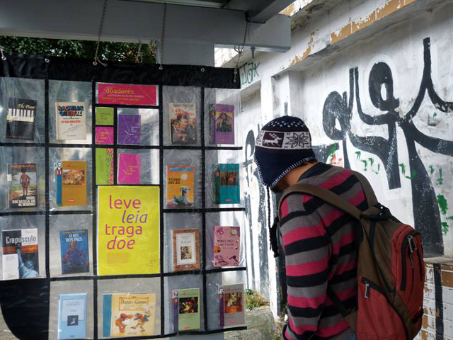 "A passenger peruses books at a ""Book Stop"" in Sao Paolo. Photo by Parada do Livro."