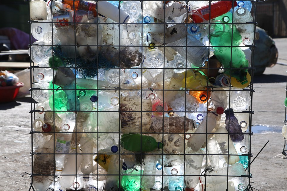 A close-up of the metal gabions filled with plastic waste.