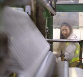 A student in high-vis jacket looks through the window at textile machinery