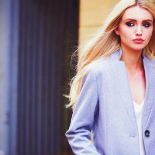 A model wears a grey tailored jacket from AVIE