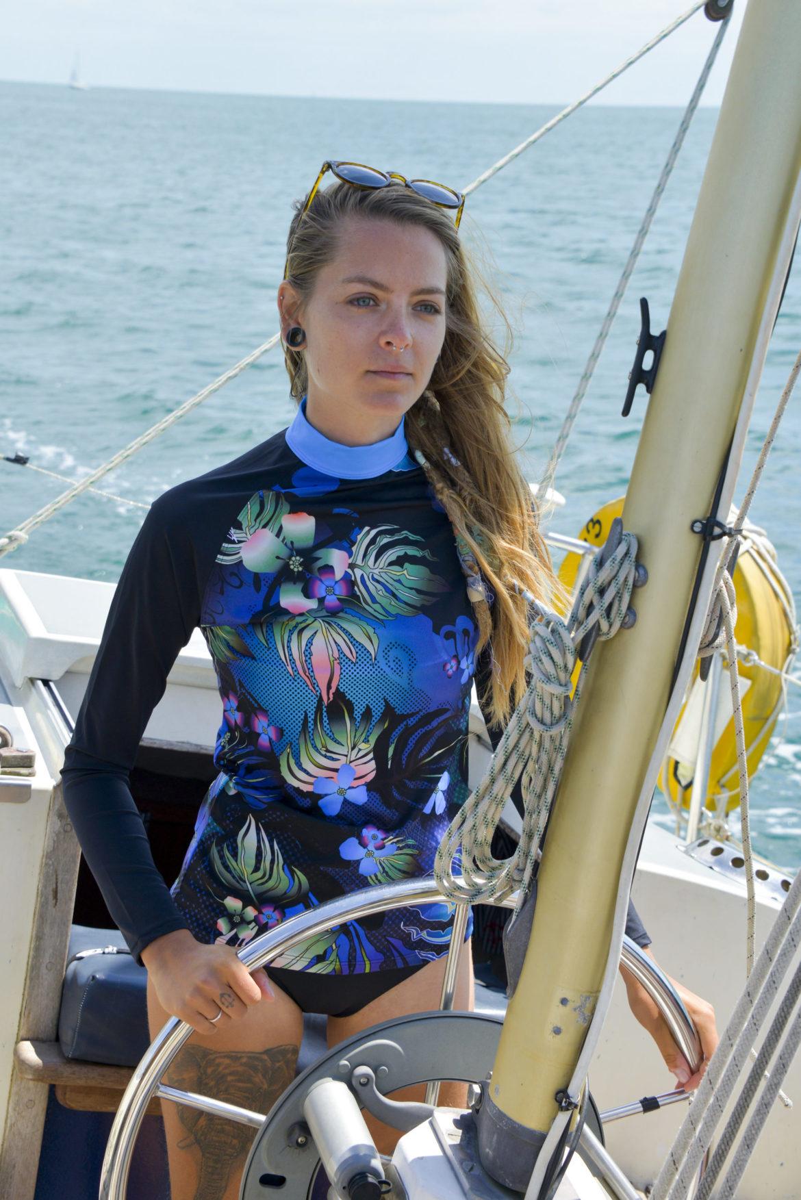 Model wears long-sleeve blue floral pattern swim top by Ruby Moon