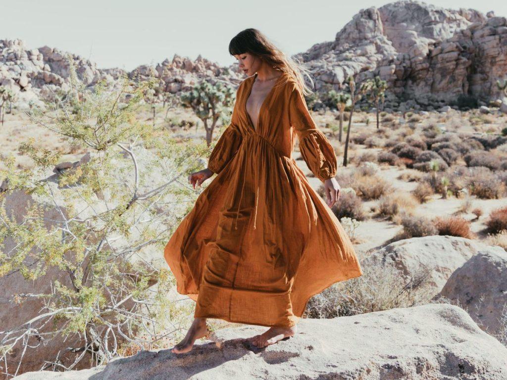 Model wears long sleeved ochre dress.
