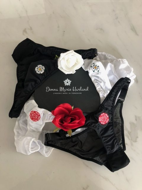 Two thongs and two pairs of briefs in both black and white, with Yorkshire and English roses embroidered on the front, draped over a black Donna Marie Harland box