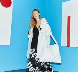 Model wears long black v-neck top undernear a white mack and oversized white handbag, along with white sneakers and long black skirt emblazoned with 'Perfect' written in a gothic script, all by Nomad Atelier