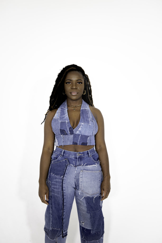 Model wears a denim patchwork halter-neck top and trousers.