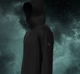 A black hooded raincoat with four buttons down the front against the backdrop of dark clouds and raindrops.