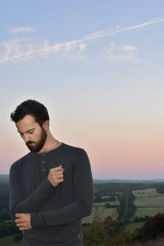 Man wearing dark grey long-sleeve top against a sunset over rolling fields