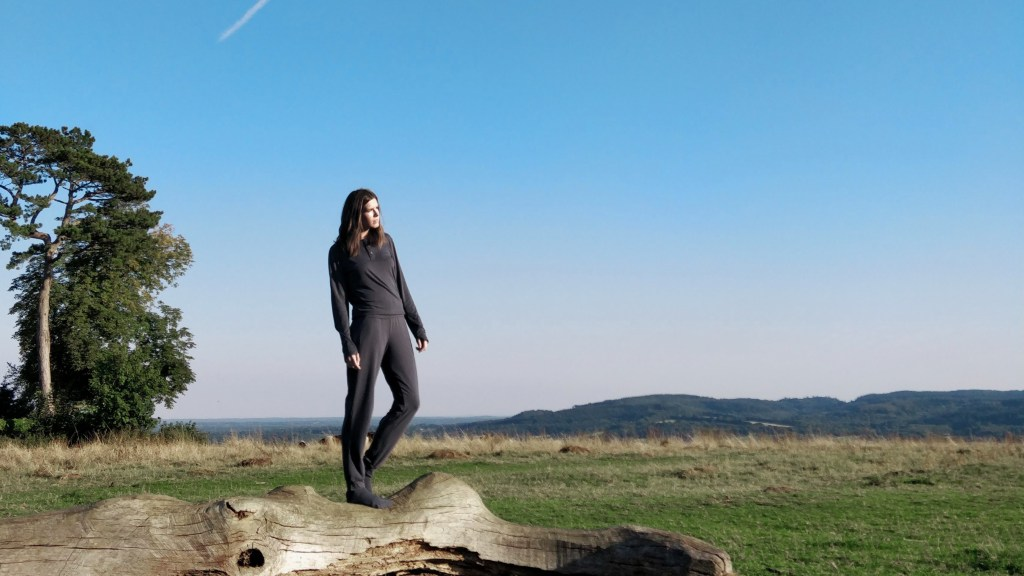 Woman wearing dark grey long-sleeve top, trousers and socks stands on a fallen tree in the middle of open countryside against a wide blue sky