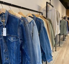 Racks of pre-loved denim jackets and shirts inside Tråd Collective