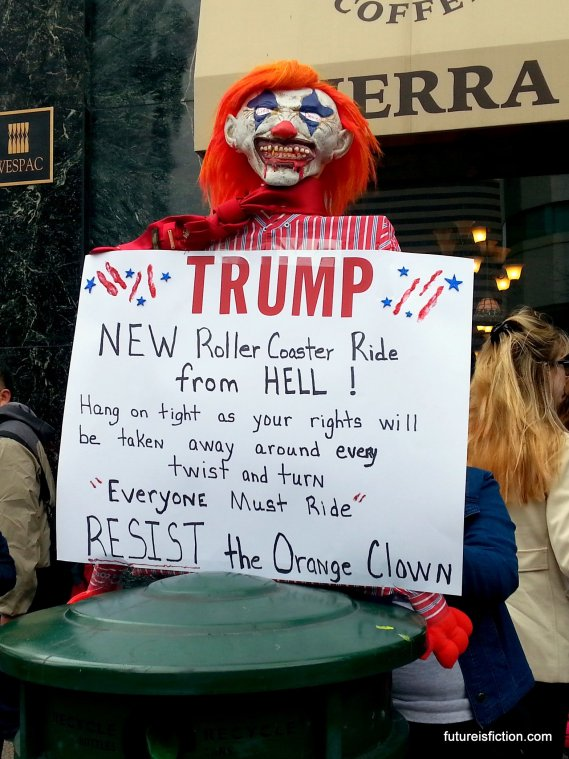 "Clown puppet with sign: ""TRUMP: New roller coaster ride from HELL! Hang on tight as your rights are stripped away at every twist and turn. Everyone must ride!"""