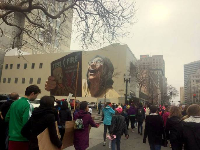 Downtown Oakland mural with Womens March in background