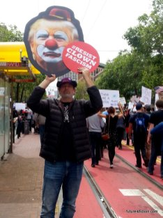 Man with a photo of Trump wearing a clown nose and a sign: Resist clown fascism