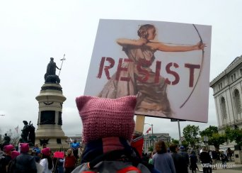 pink pussy hatted protester with a RESIST sign