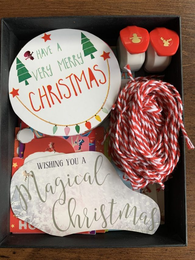 Christmas card gift tags, hole punches and red & white cord stored together in a black box.