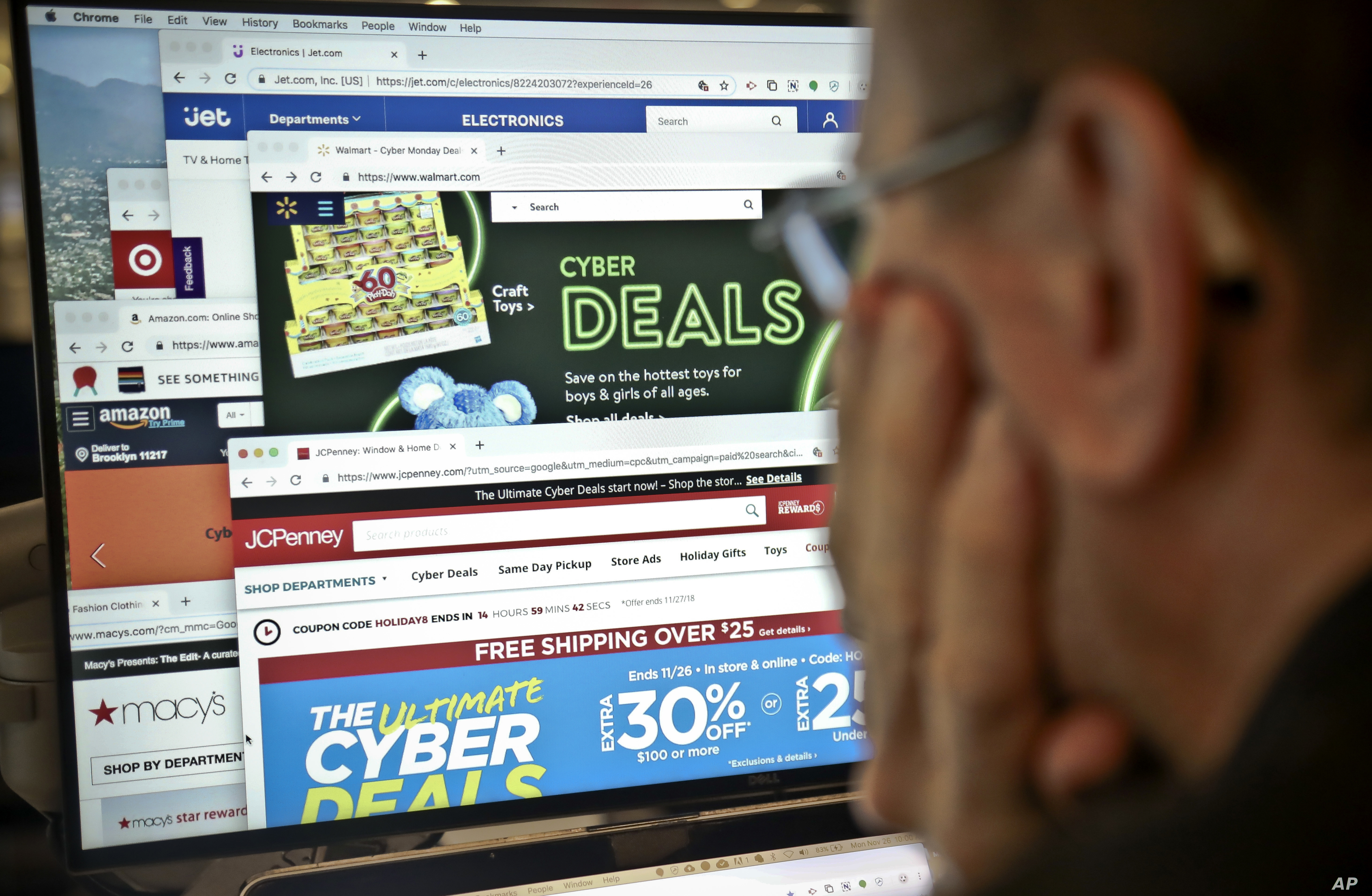 A journalist looks at a computer screen with webpages arranged to show Cyber Monday deals by various online retailers Monday Nov. 26, 2018, in New York. The physical rush of Black Friday and the armchair browsing of Cyber Monday are increasingly…