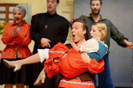 Nathaniel Olsson and Carley Miller (along with various cast members in the background) have fun on stage!