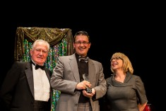 """Past President Dann Wilhelm accepts the award for Best Choreographer on behalf of Carol Seitz who won for her work in """"Santa Claus The Panto""""."""