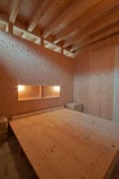 神戸町の家 寝室の壁は構造用合板、床はコンクリートの土間。置かれた構造用合板はベッドのマットを敷きます