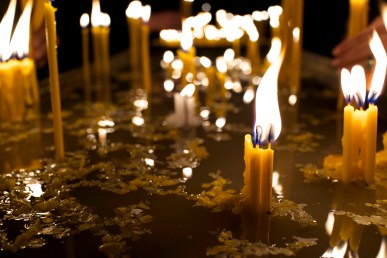 Lit candles melt into a pool of wax.
