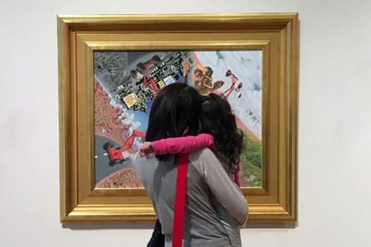 A mother holds her child in her arms, her back facing the camera, as they view a work of art on display.