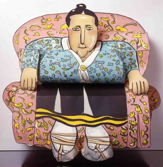 Gertrude is the name of the woman sitting on a flower printed, pink chair. Her black hair is pulled up in a bun and she wears a printed blouse and black skirt with a yellow trim.