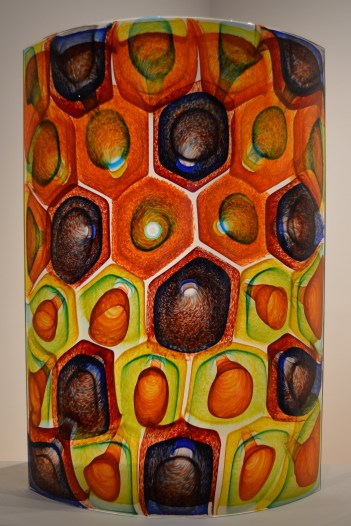 This glass piece looks like snake scales in colors of orange, green, blue, yellow, and purple wrapping around its thick vase-shape.