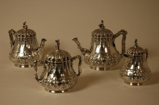 A silver tea pot, coffee pot, and sugar pot.