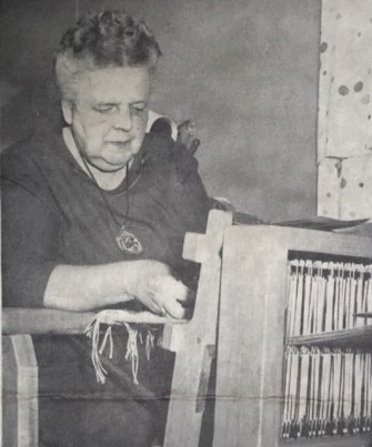 Blanche Hutto sits in front of her loom and weaves in this photograph.
