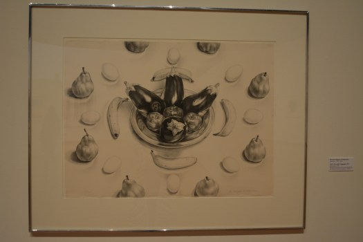 This lithograph by Erlebacher is a still life of fruits and vegetables. In the center is a bowl with four eggplants and three apples. Surrounded by that are four bananas laid on their side, then around that are pears and eggs alternating.