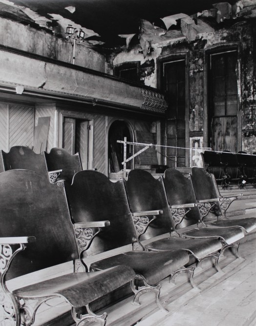 The black and white photo shows a run-down theatre in Indiana. The paint is peeling off the walls and parts of the ceiling have fallen in. Boards are resting against the back wall. In front, the seats are all aligned and dusty, showing its lack of use.
