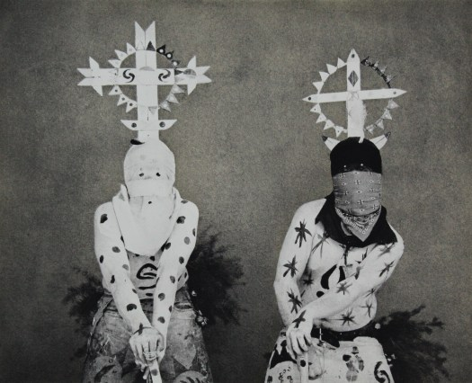 Two Apache dancers are the focus of this photo. They are crouched holding sticks in their clasped hands, dancing side-by-side. They wear a hood and bandanna, respectively, covering their faces. Their clothes are painted with dots and other symbols.