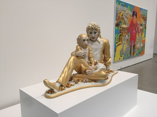 A gold statue of Micheal Jackson holding a monkey.