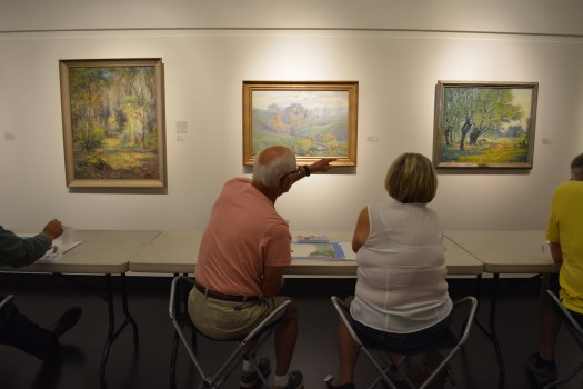 Visitors examine paintings by Indiana Impressionist painters.