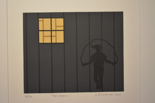 The silhouette of a girl jumps rope in front of a fence with a window in it, meant to show a Japanese internment camp.