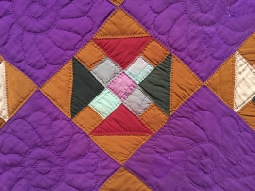 A close up shot of another quilt, this one has a purple background with a stitched flower inlaid. Every other triangle has a brown background with a patchwork pattern.