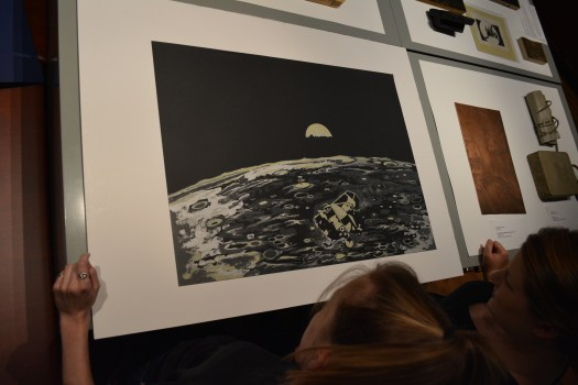 "Two visitors look down at Nesbitt's ""Moon Shot"", which shows the surface of the moon, the Earth in the distance, and the space shuttle flying overhead."